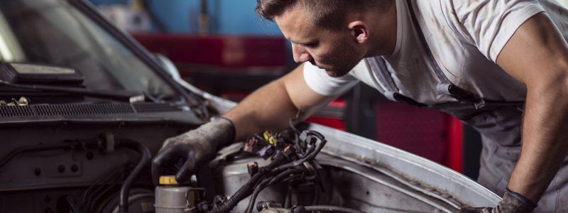 Close-up of auto mechanic repairing car engine